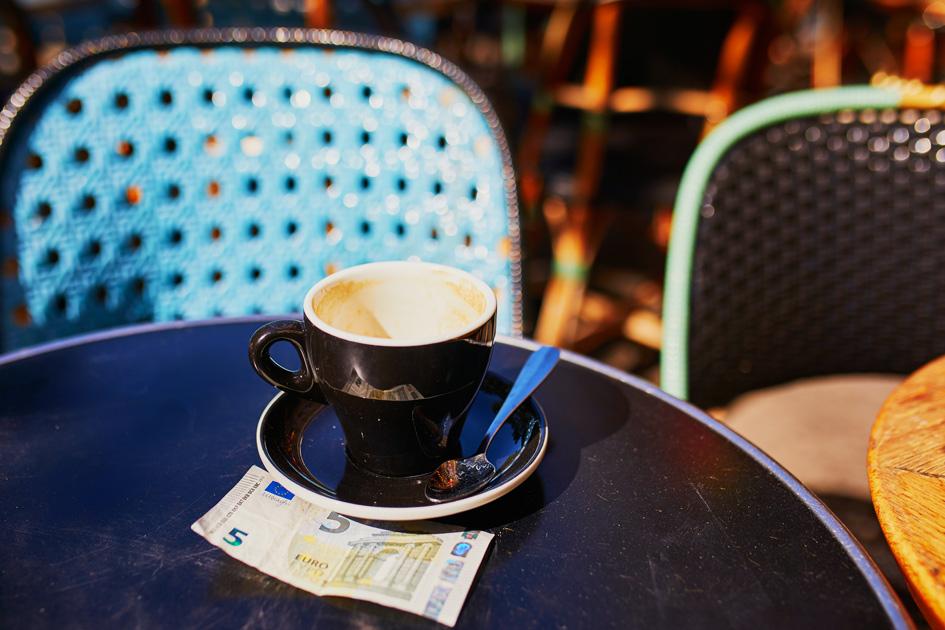 Leere Kaffeetasse auf einem Tisch mit fünf Euro Schein