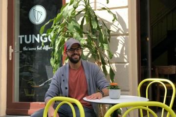 Hussein, der Besitzer der Gastronomie Tungos, sitzt lächelnd in seinem Außenbereich