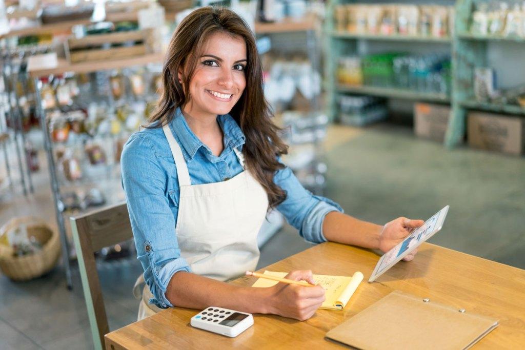 Junge Kellnerin sitzt am Tisch und lächelt und lernt für die Befähigungsprüfung im Gastgewerbe