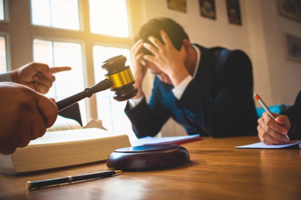 Ein verzweifelter Mann in Anzug sitzt vor Gericht und im Vordergrund wird ein Hammer geschlagen