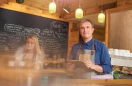 Ein Gastronom mit einem iPad Kassensystem blickt der Kassensicherungsverordnung entspannt entgegen.