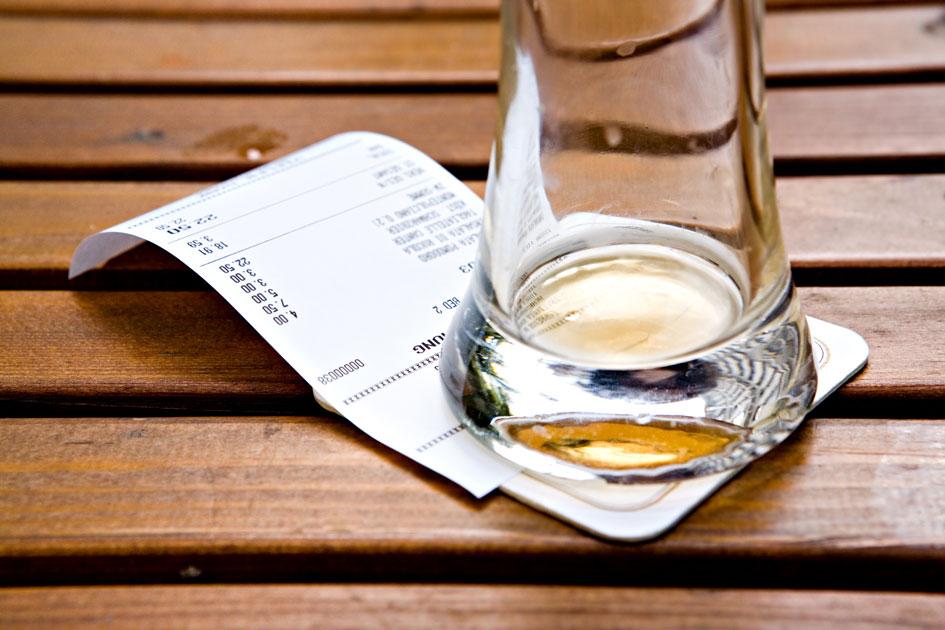 Ein Beleg auf dem Tisch unter einem ausgetrunkenem Bierglas.