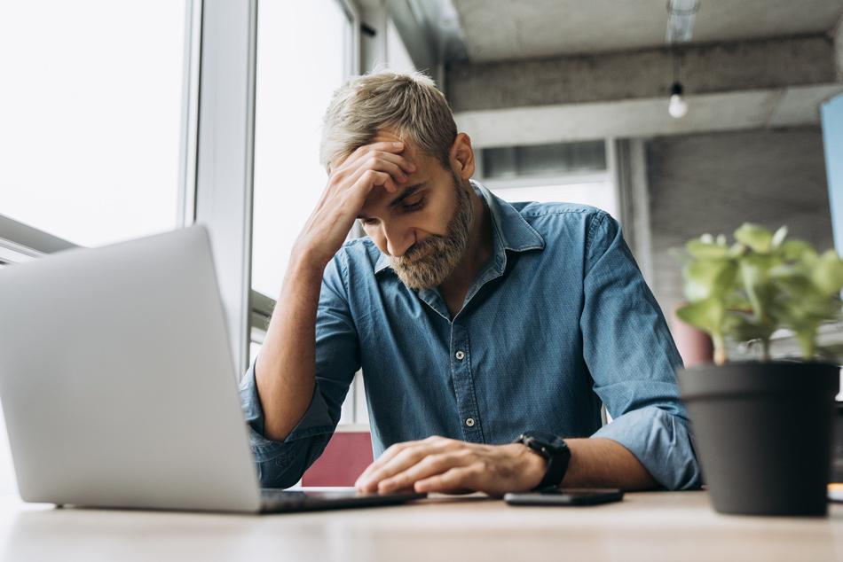 Ein Mann sitzt vor dem Laptop und hat seinen Kopf verzweifelt auf der Hand gestützt.