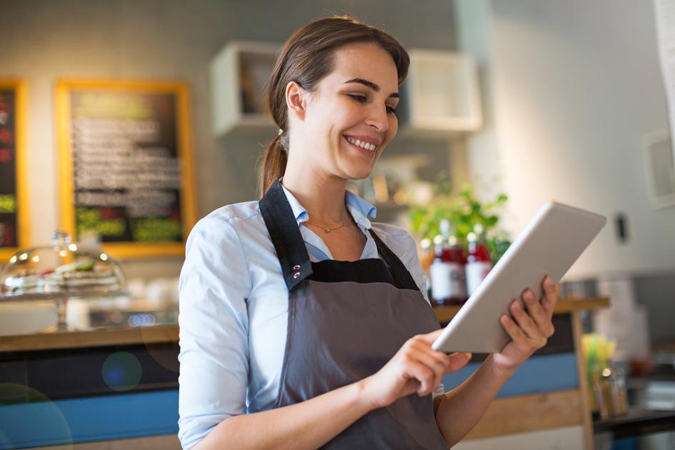 Gastronomin tippt lächelnd auf einem iPad-Kassensystem.