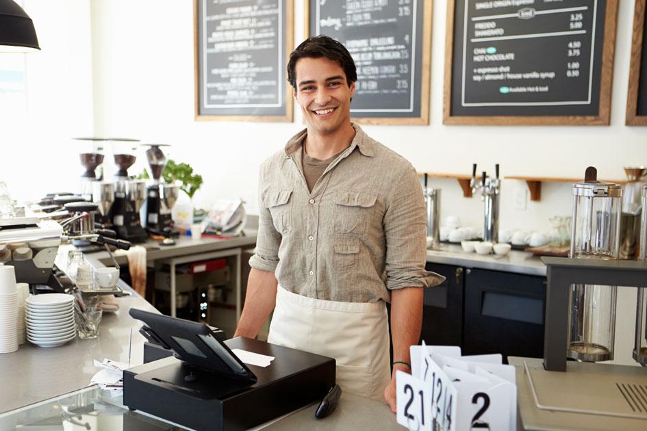 Ein lächelnder männlicher Gastronom mit einer iPad Kasse hinter dem Tresen.