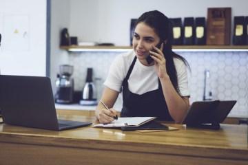 Eine Gastronomin telefoniert mit dem Finanzamt, um der Kassenmeldepflicht nachzukommen.