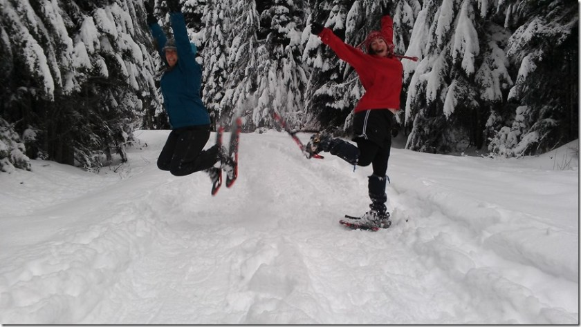 Two women jumping in a snowy forest wearing snowshoes