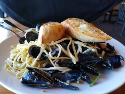 A plate of pasta with mussels and bread
