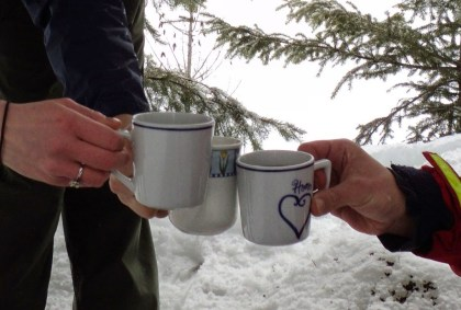 three mugs of hot drinks in a snowy forest