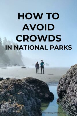 Foggy and sunny beach with rocks and two people. How to avoid crowds in national parks is printed on the photo