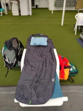 A sleeping bag, pad and pillow are on a lounge chair laying flat on the deck of the Alaska ferry. Luggage is sitting next to it.
