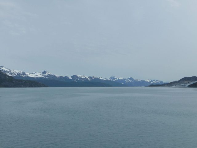 Distant snow capped mountains frame the water of Glacier Bay