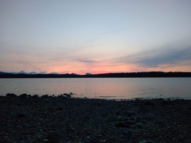 A pink sunset behind distant mountains and a forested island. In the foreground is the beach in the campground at Bartlett Cove campground to visit Glacier bay national park