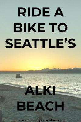 A sunset behind mountains. In the foreground is water and a beach, with a single fishing boat. Text reads: Ride a bike to Seattle's Alki beach