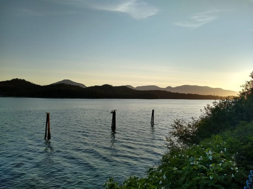 A sunset behind forested hills along the water. In the foreground are three pilings in the water