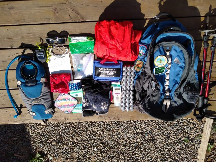 A blue backpack and lots of day hiking gear, including trekking poles, a red rainjacket, a first aid kit, a sit pad, head net, water bladder, sunglases and a map