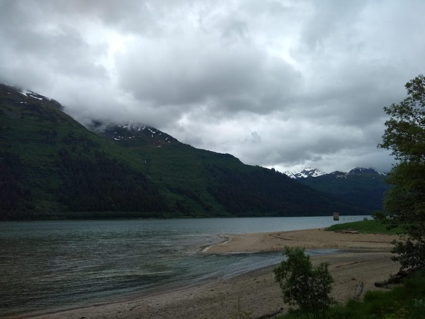 Forested mountains covered in clouds across a narrow body of water. In the foreground is a sandy beach with some trees nearby