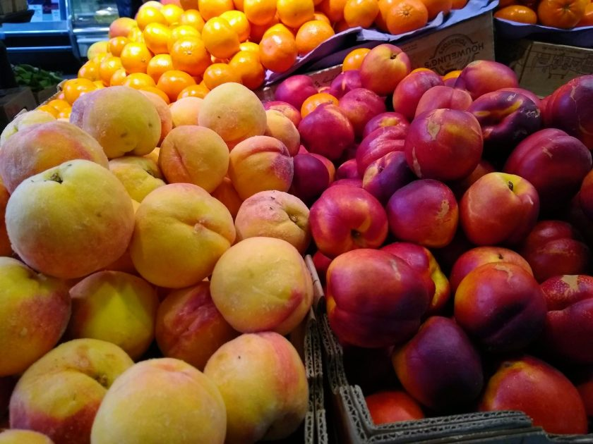 Yellow peaches are in a box to the left and red orange nectarines are in a box next to them at a market.