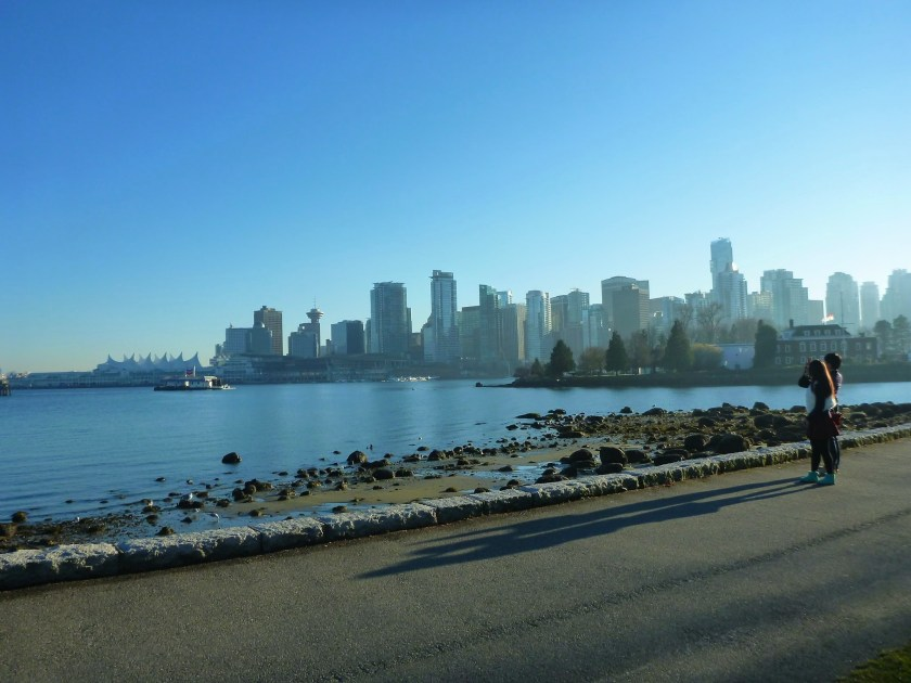 A city skyline is seen in the distance across a body of water. In the foreground is a paved trail and a rocky beach. It's a blue sky sunny day