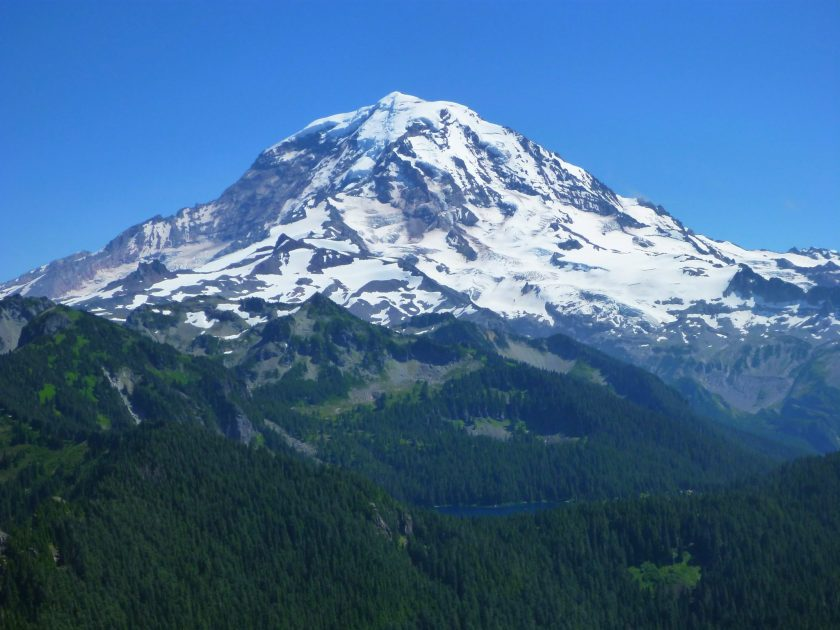 The Tolmie Peak Lookout hike has epic views of Mt Rainier. Here it is filling the frame against a clear blue sky with forested hillsides in the foreground
