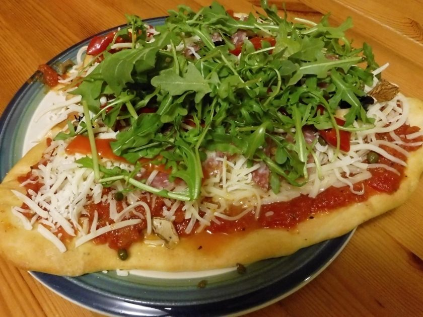 A homemade pizza is on a plate on a wooden table. The pizza has red sauce, white cheese and greens on top