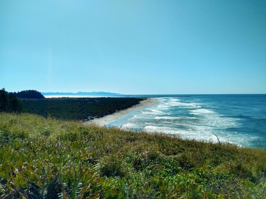 A sandy beach is below a green hill. There are waves breaking on the beach. In the distance is a river mouth and beyond that, mountains