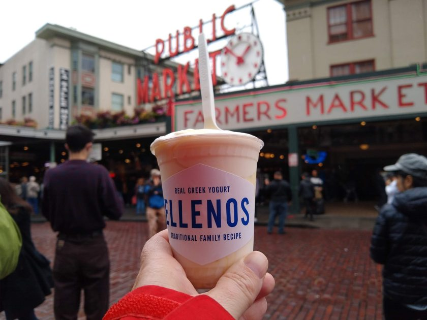 A person's hand holding a small plastic cup of yogurt in front of out of focus people and signs of Pike Place Market