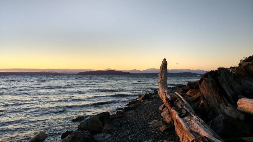 A winter sunset behind distant mountains. There are islands in the foreground and driftwood on the gravel beach.