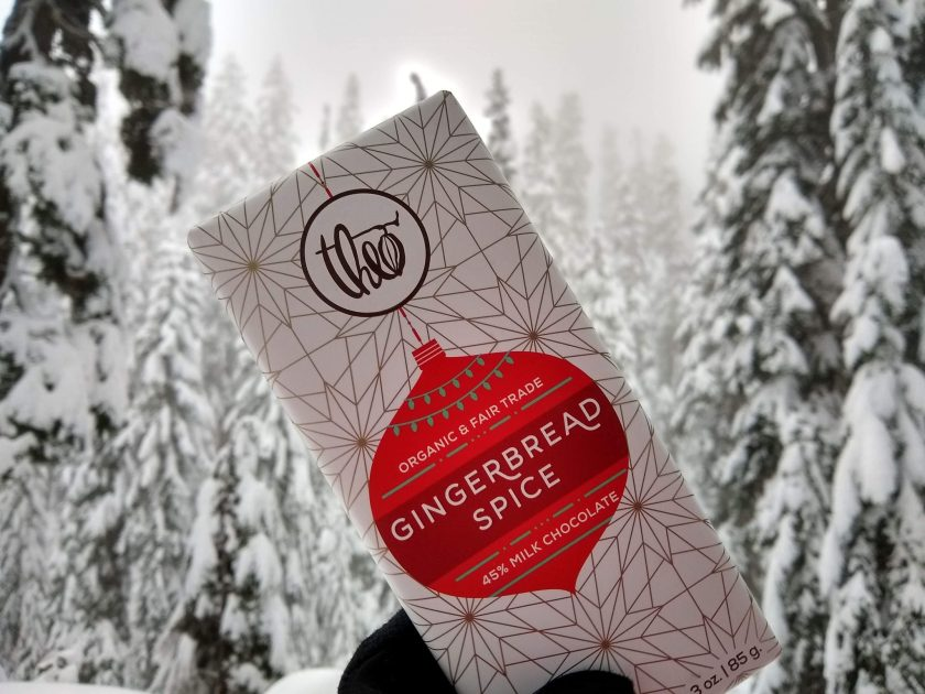 Snow covered evergreen trees in the background. In the foreground, a gloved hand is holding a theo chocolate bar which is gingerbread spice flavored. One of the suggested amazon gifts for outdoorsy women 2019!