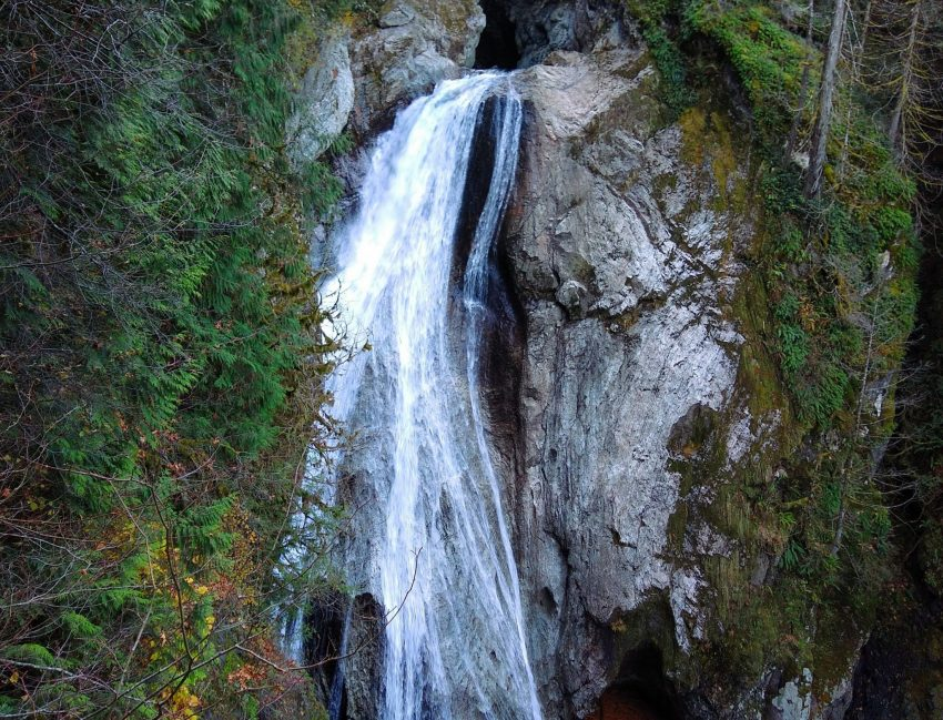 A wide and high waterfall cascades over a vertical rock face. There are trees and green shrubs around it