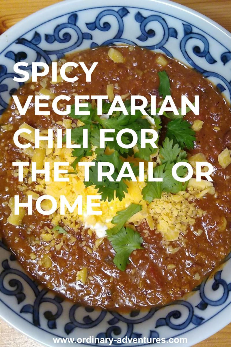 A bowl of spicy vegetarian chili with cheese and cilantro on top. It's in a blue and white bowl on a wooden table.