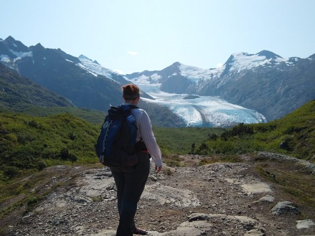 A woman is standing at the top of Portage Pass, one of the best things  to do in Alaska! She is facing away towards Portage Glacier in the background against snow covered mountains. She is surrounded by meadows. She has gray hiking pants, a long sleeved white shirt and a blue backpack
