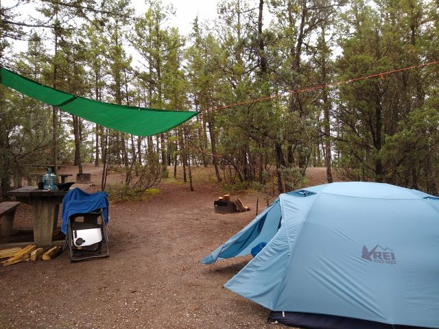 A blue tent in a campsite surrounded by trees. There is also a fire pit, firewood, a camp chair and a tarp