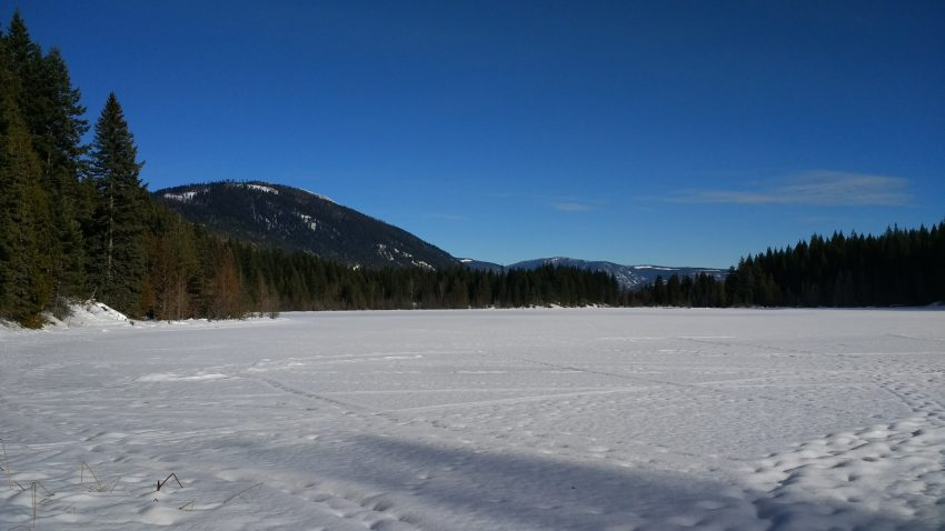 A frozen lake on a sunny day surrounded by hills near Kamloops BC