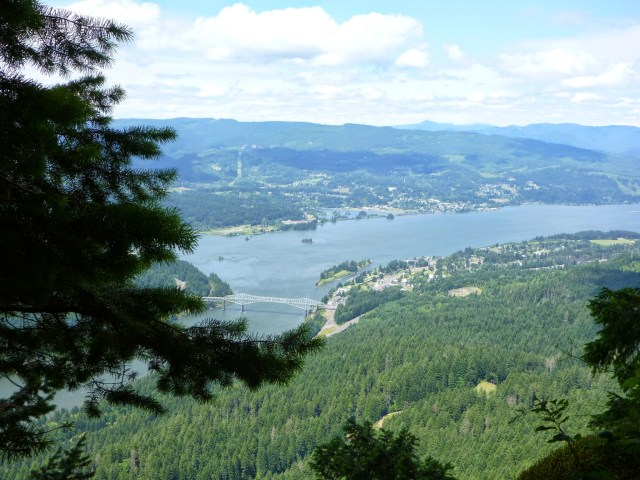 The Columbia River Gorge, a weekend getaway from Seattle is seen from high on a mountain above the river. There are evergreen trees on the mountain and below you can see a town and a large bridge