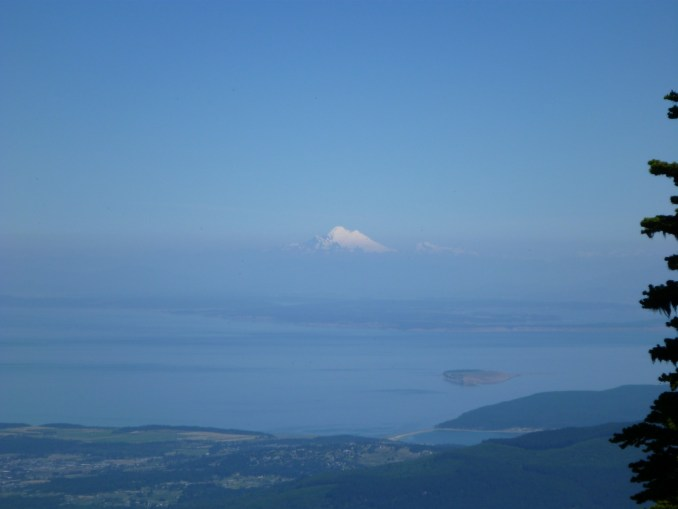 A high, snow covered mountain in the distance and water and islands in the foreground
