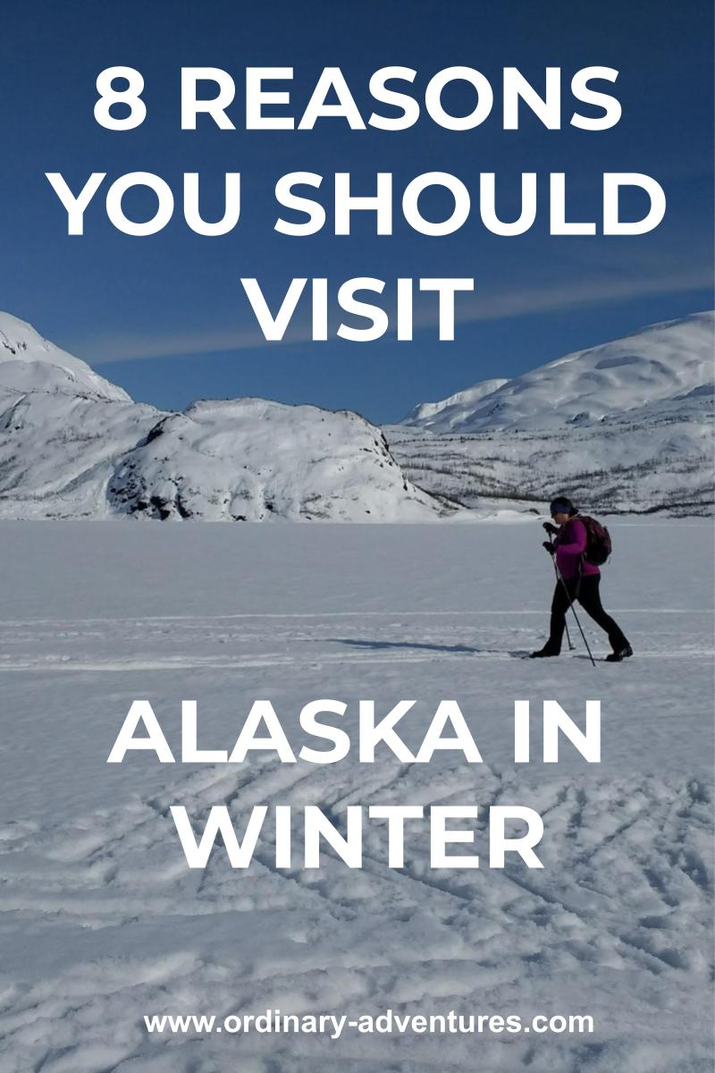 a person skis across a frozen lake in winter in alaska. It's a sunny blue sky day and there are mountains surrounding the lake. Text reads 8 reasons you should visit Alaska in winter