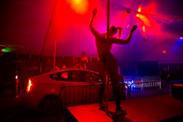 After first offering food delivery, the Lucky Devil Lounge strip club has started a second venture: food pickup via a drive-thru strip club. Four go-go dancers perform under cover of an outdoor tent in the club parking lot, while customers wait for their orders in their cars. Owner Shon Boulden is calling it Food 2 Go-Go. April 17, 2020 Beth Nakamura/Staff