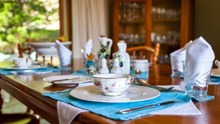 A family dining room table, set with china and crystal reflects family memories.