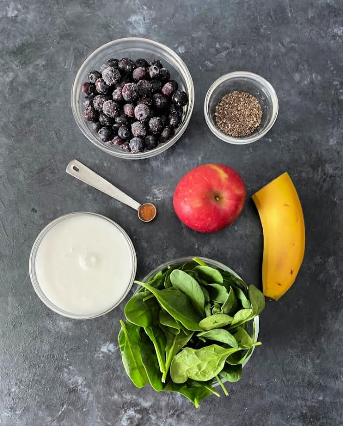 Blueberry Detox Smoothie ingredients laid out - blueberries, chia seeds, coconut milk, cinnamon, apples, banana, and spinach.