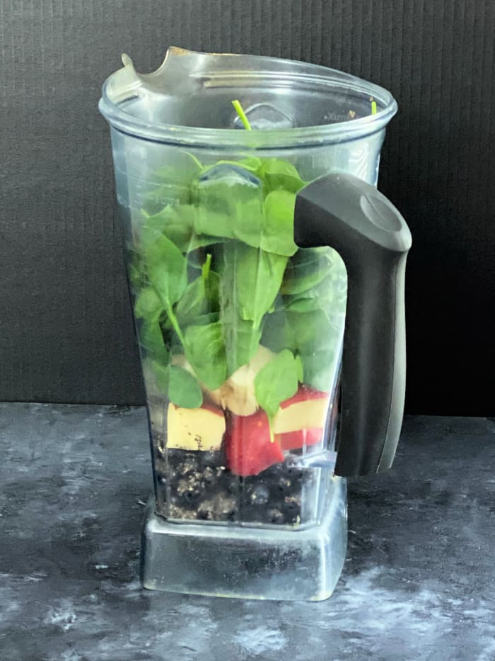 Blueberry banana smoothie topped with spinach in a blender container.