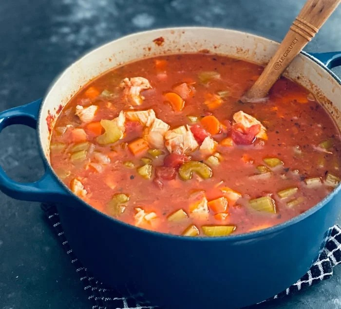 Blue pot of detox soup with chunks of chicken, celery, tomatoes, celery, and carrots.