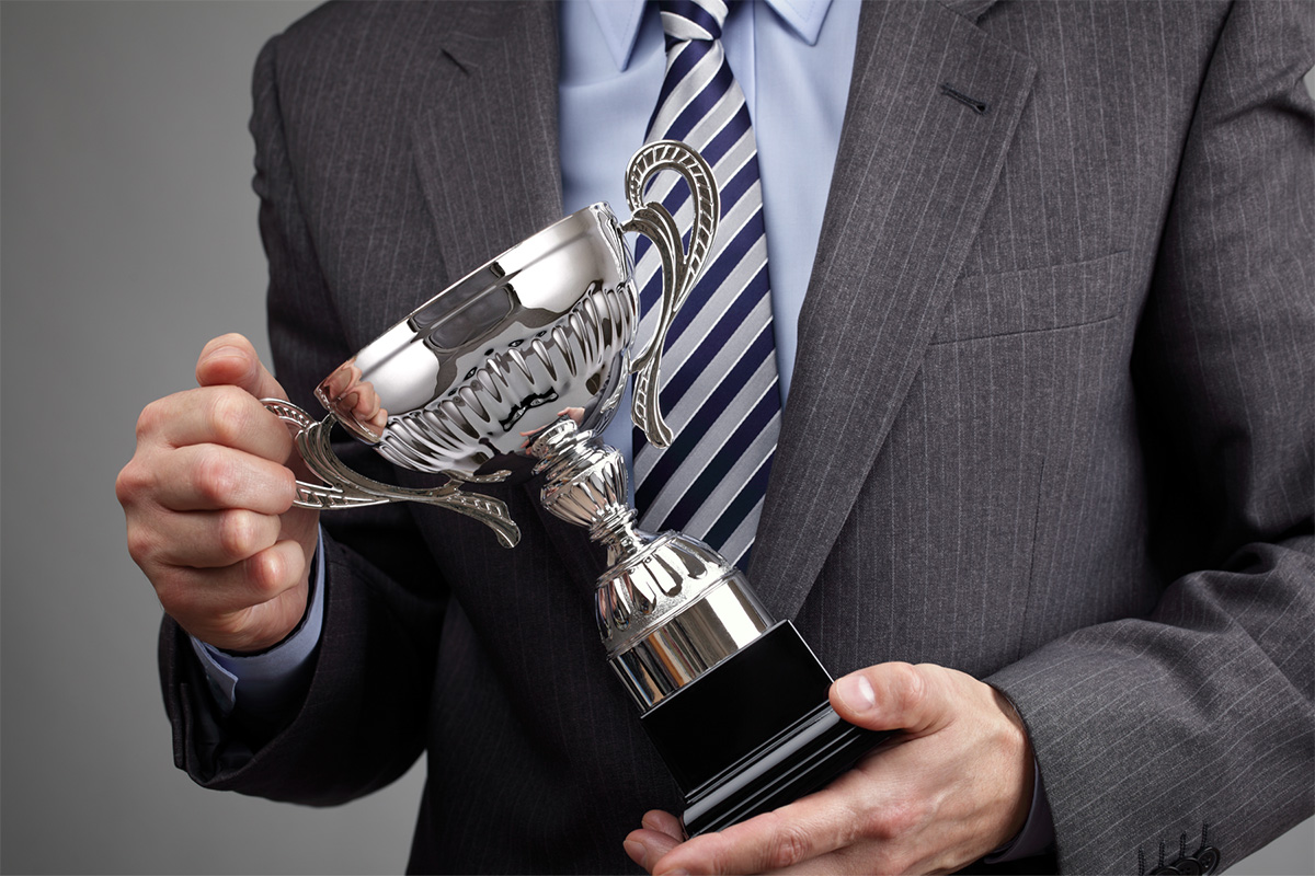 Image of a man holding an award
