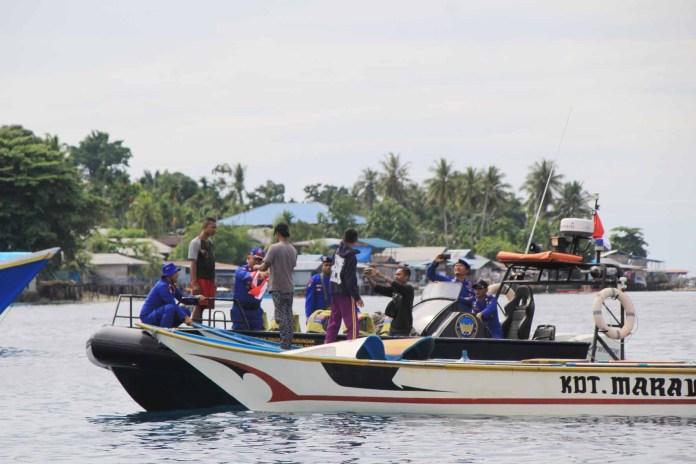 Polair Polres Manokwari Bagi Ratusan Bendera Bagi Nelayan dan Taksi laut