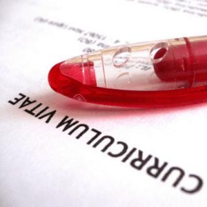 imagen de un curriculum y bolígrafo rojo