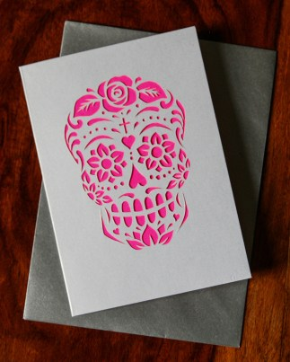 A calavera design cut out of pearlescent card, with a flourescent pink backing, consisting of flowers, hearts and swirls