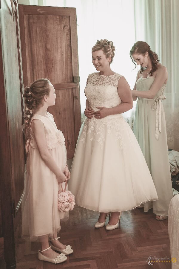 Bridesmaid and baby help help the bride dress up