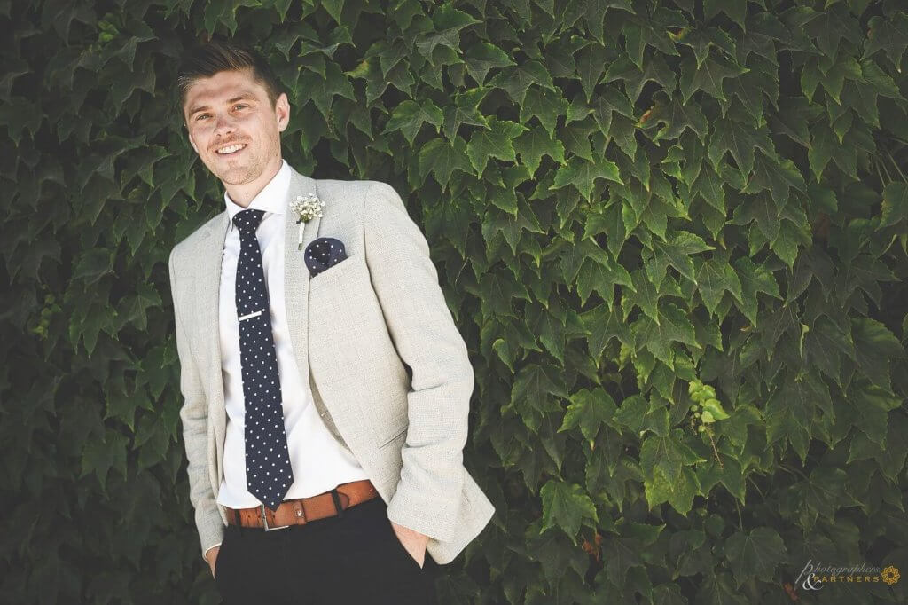 The groom stands in front of ivy leaves
