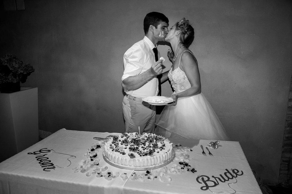 Lauren & Ben kiss after cutting the cake