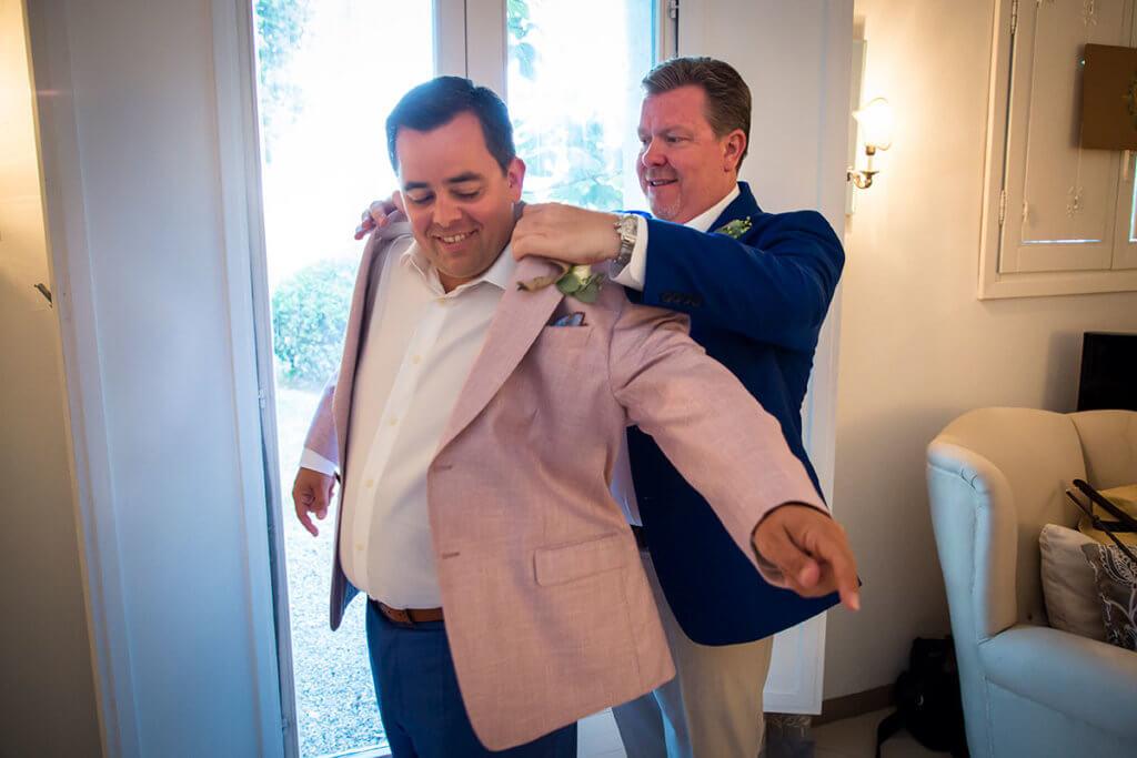 Dan helps Tim to wear his jacket